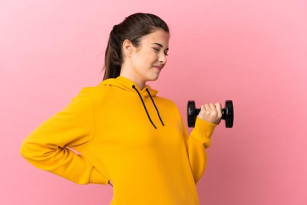 Chica joven deporte haciendo levantamiento de pesas sobre fondo rosa aislado que sufre de dolor de espalda por haber hecho un esfuerzo