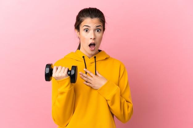Chica joven deporte haciendo levantamiento de pesas sobre fondo rosa aislado sorprendido y conmocionado mientras mira a la derecha