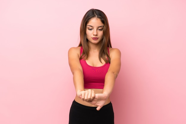 Chica joven deporte sobre brazo estiramiento rosa aislado