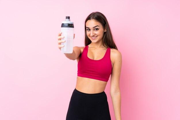 Chica joven deporte sobre rosa aislado con botella de agua deportiva