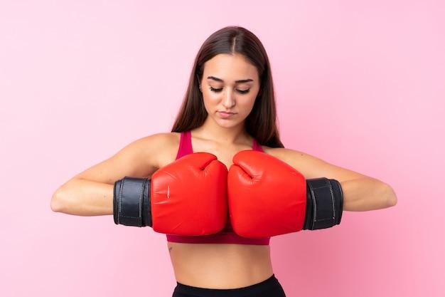 Chica joven deporte sobre rosa aislado con guantes de boxeo