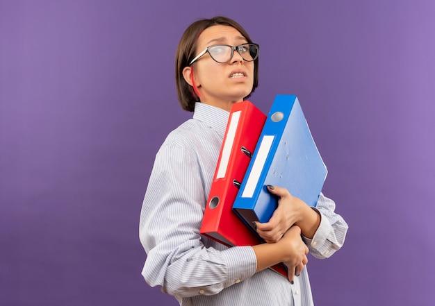 Chica joven descontenta del centro de llamadas con gafas sosteniendo carpetas aisladas sobre fondo púrpura con espacio de copia
