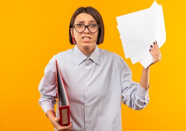 Chica joven descontenta del centro de llamadas con gafas sosteniendo el portapapeles y levantando documentos aislados sobre fondo naranja
