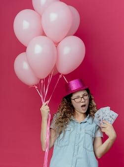 Chica joven descontenta con gafas y sombrero rosa sosteniendo globos y dinero en efectivo aislado en rosa