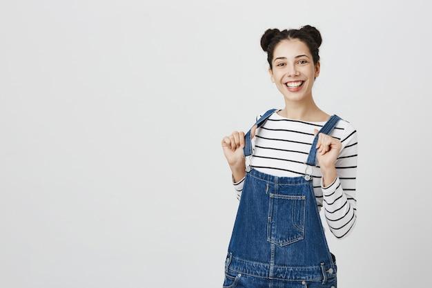 Chica joven despreocupada con peinado de bollos mirando feliz
