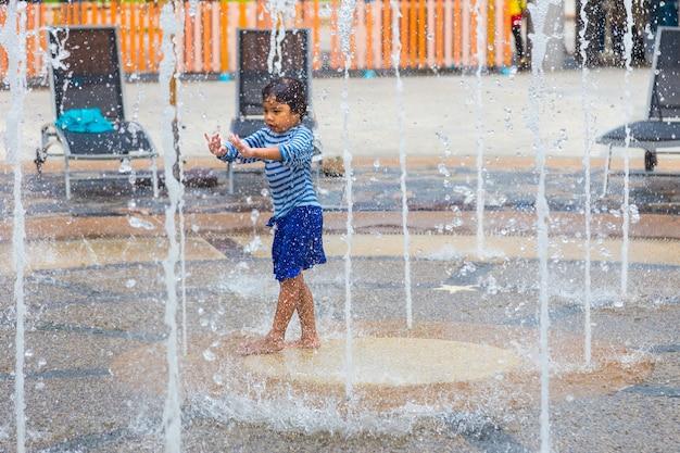 Chica joven disfruta jugando con agua de tiro en el área de la fuente de agua en splash jungle wate