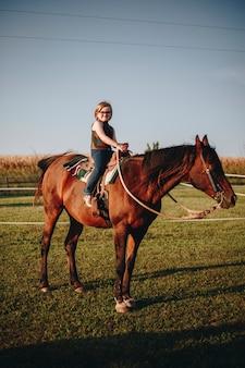 La chica joven está disfrutando de una equitación