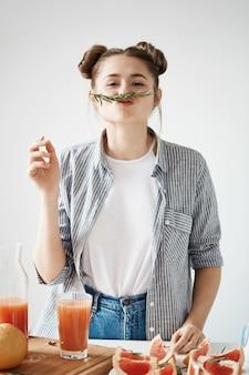Chica joven divertida con los bollos que hacen el bigote con el brunch del romero que prepara el smoothie sano de la desintoxicación del pomelo sobre la pared blanca.