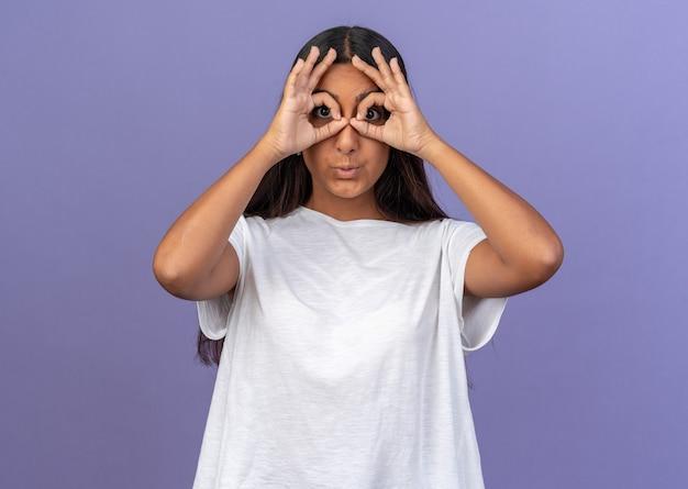 Chica joven divertida en camiseta blanca mirando a la cámara a través de los dedos haciendo gesto binocular de pie sobre fondo azul.