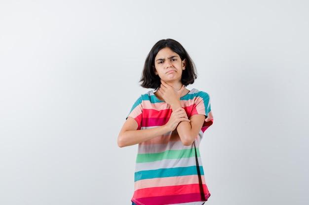 Chica joven con dolor de cuello en camiseta a rayas de colores y mirando exhausto, vista frontal.