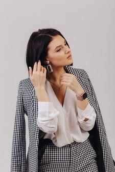 Chica joven elegante atractiva en ropa de negocios posando en la pared de luz en estudio. concepto de ropa elegante y sofisticación.