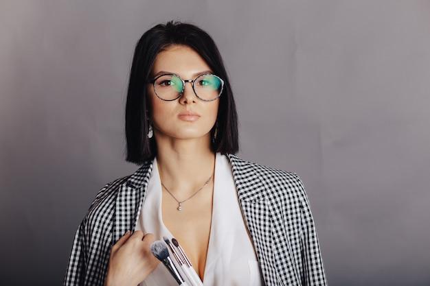 Chica joven elegante atractiva en ropa de negocios posando en la pared oscura. concepto de ropa elegante y sofisticación.
