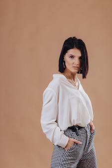 Chica joven elegante atractiva en traje de negocios posando en la pared de crema. concepto de ropa elegante y sofisticación.