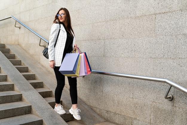 Chica joven elegante con bolsas multicolores después de ir de compras baja las escaleras.