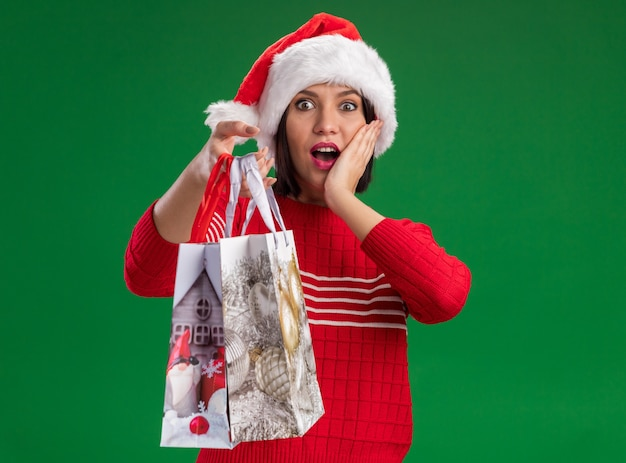 Chica joven emocionada con gorro de papá noel sosteniendo bolsas de regalo de navidad manteniendo la mano en la cara aislada en la pared verde
