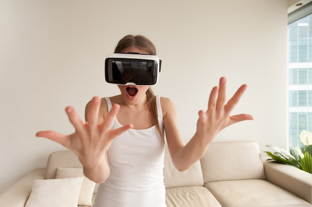 Chica joven emocionada sorprendida que lleva los vidrios de vr que miran las manos