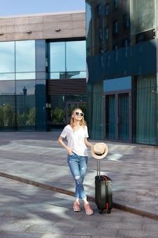 Chica joven con equipaje en verano cerca del edificio