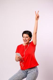 Chica joven escuchando música en el teléfono y bailando.