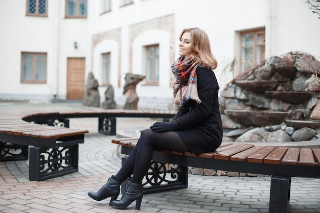 Chica joven con estilo en una bufanda y abrigo negro sentado en un banco