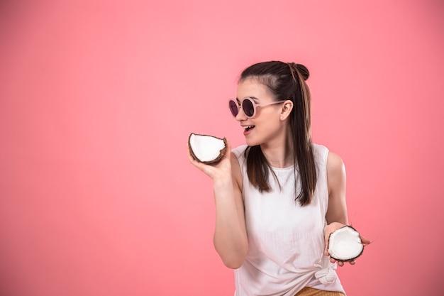 Chica joven con estilo en gafas de sol sonríe y sostiene frutas sobre un fondo rosa. concepto de vacaciones de verano.
