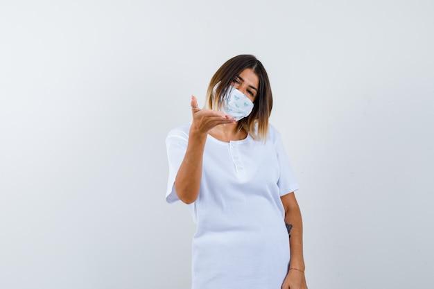 Chica joven estirando la mano como sosteniendo algo imaginario en camiseta blanca, máscara y mirando alegre. vista frontal.