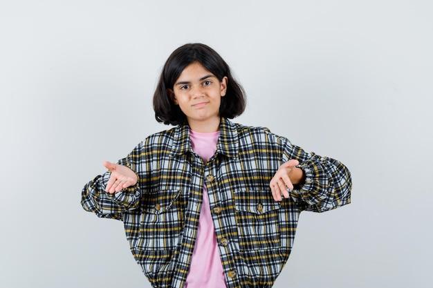 Chica joven estirando las manos como invitando a entrar en camisa a cuadros y camiseta rosa y luciendo amable. vista frontal.