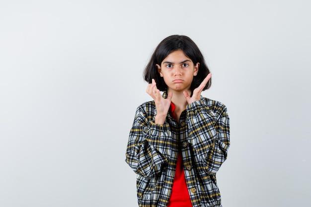 Chica joven estirando las manos como sosteniendo algo en camisa a cuadros y camiseta roja y luciendo lindo. vista frontal.