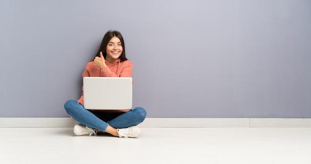 Chica joven estudiante con una computadora portátil en el piso dando un gesto de pulgares arriba