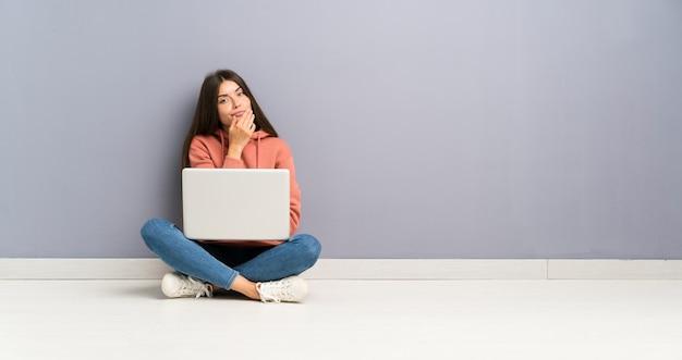 Chica joven estudiante con una computadora portátil en el piso pensando en una idea