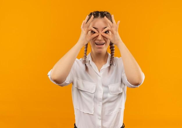 Chica joven estudiante en gafas con coletas en camisa blanca mirando hacia el frente haciendo letrero binocular con los dedos sonriendo mirando a través de este letrero parado sobre la pared naranja