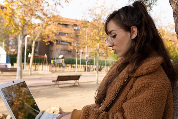Chica joven estudiante con gafas trabajando con su computadora portátil en el parque.