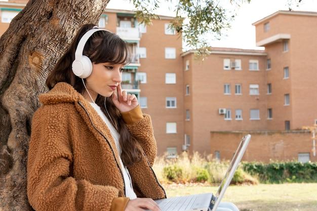 Chica joven estudiante haciendo una videoconferencia con su computadora portátil en el parque.