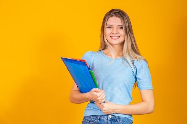 Chica joven estudiante con libros sobre fondo amarillo. de vuelta a la escuela.