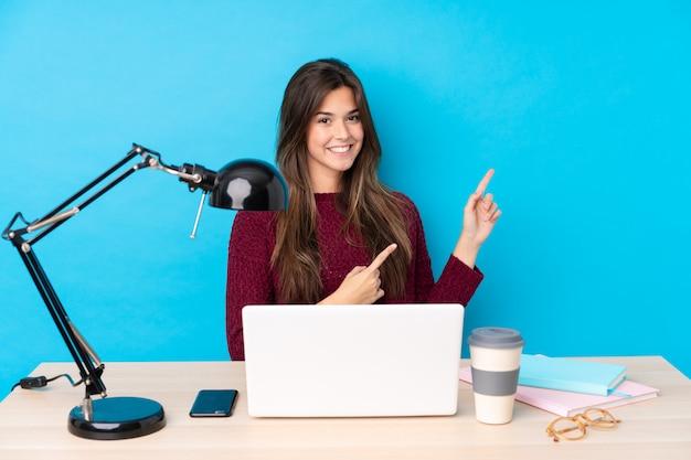 Chica joven estudiante en un lugar de trabajo sobre pared azul