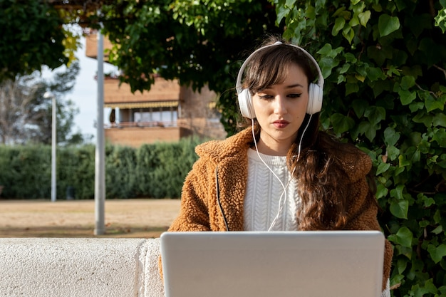 Chica joven estudiante trabajando con su computadora portátil en el parque.
