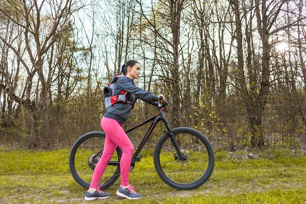 Chica joven de excursión con su bicicleta