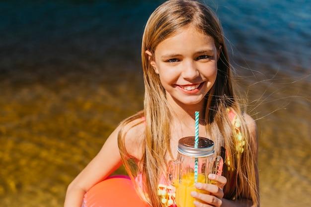 Chica joven feliz con bebida de naranja en vacaciones en la playa