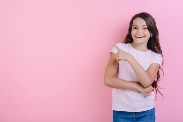 La chica joven feliz con las manos dobladas se coloca señalando su dedo en lado y mirando la cámara.