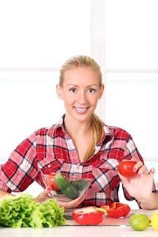 Chica joven y feliz preparando comida saludable