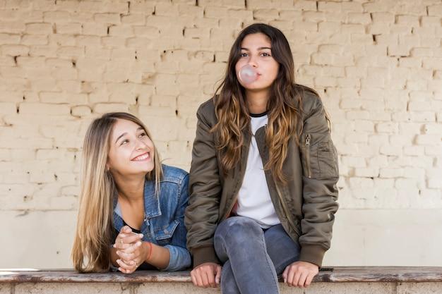 Chica joven feliz que mira a su amigo que sopla el chicle