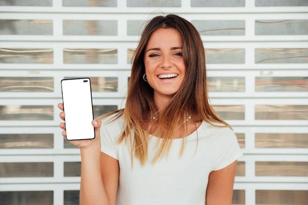 Chica joven feliz que sostiene smartphone
