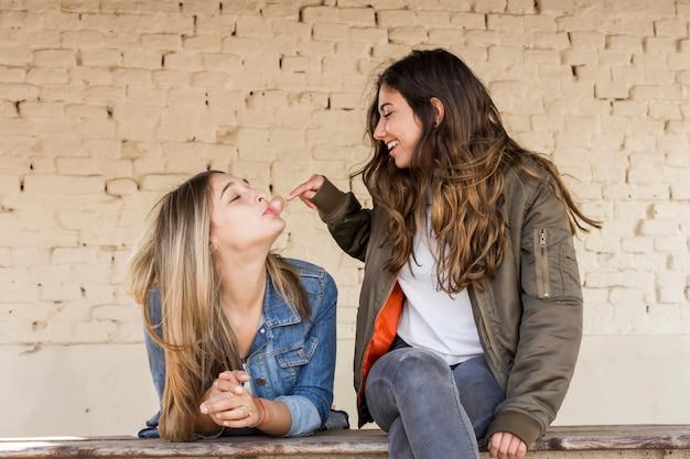 Chica joven feliz que toca una burbuja soplada por su amigo con el chicle