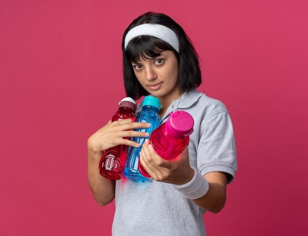 Chica joven fitness llevar diadema sosteniendo botellas de agua ofreciendo uno de ellos mirando a la cámara con rostro serio sobre rosa