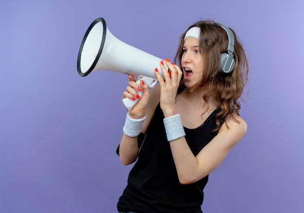 Chica joven fitness en ropa deportiva negra con diadema y brazalete de teléfono inteligente gritando al megáfono de pie sobre la pared azul