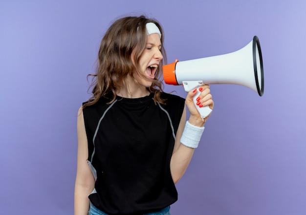 Chica joven fitness en ropa deportiva negra con diadema gritando al megáfono con expresión agresiva de pie sobre la pared azul