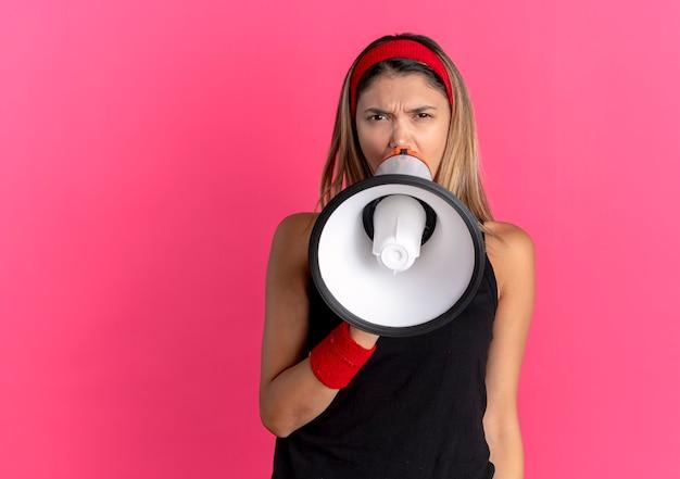 Chica joven fitness en ropa deportiva negra y diadema roja gritando al megáfono parado sobre la pared rosa
