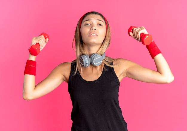 Chica joven fitness en ropa deportiva negra y diadema roja trabajando con mancuernas mirando confiado sobre rosa