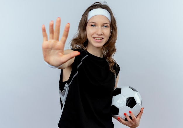 Chica joven fitness en ropa deportiva negra con diadema sosteniendo un balón de fútbol haciendo señal de stop con la mano abierta sonriendo de pie sobre la pared blanca