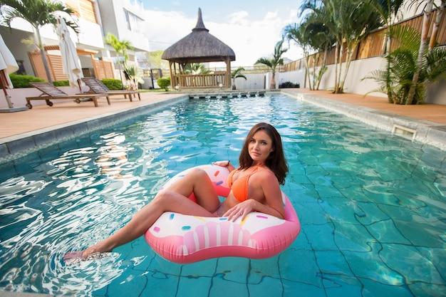 Chica joven en flotador donut rociado en la piscina