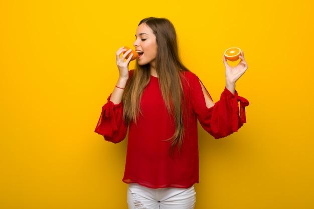 Chica joven en fondo amarillo vibrante con las naranjas